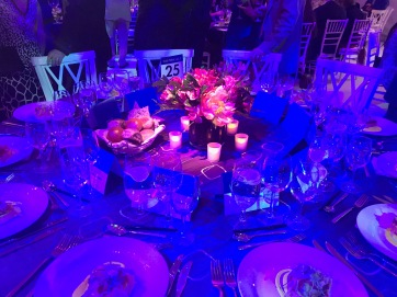 The dinner table. The table settings are white but they look blue because of the lightening. There are candles and flowers as center pieces.