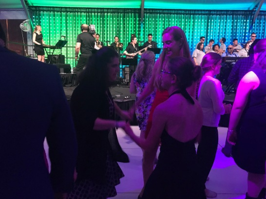 Miranda, Lizzy, Helene dancing at the gala. They are wearing dresses and holding hands as they dance. There is a live band playing in the background.