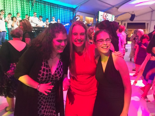 Miranda, Helene and Lizzy smiling with their arms around each other.